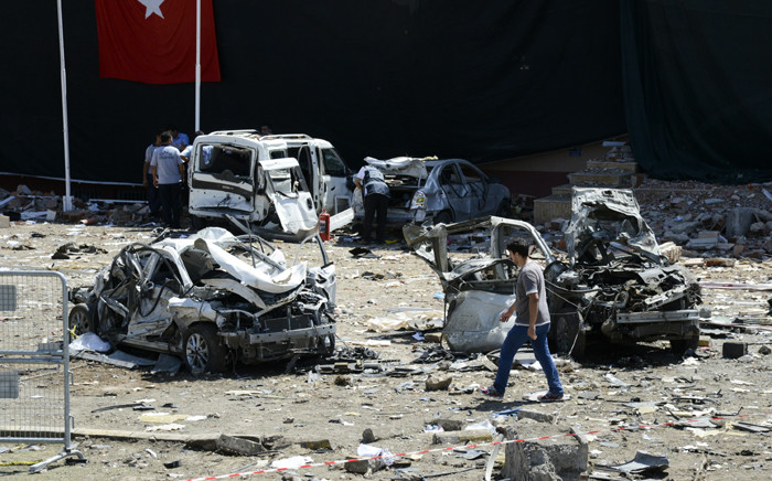 FILE: Turkish rescue workers stand by the wreckage of a vehicle as a police officer inspects a destroyed car. Picture: AFP.
