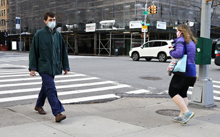 FILE: Two people wearing protective masks pass on the street during the COVID-19 pandemic on 21 April 2020 in New York City. Picture: AFP.