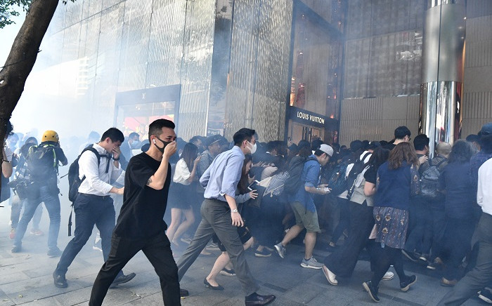 People react after tear gas was fired by police during a protest in Hong Kong on 11 November 2019. Picture: AFP