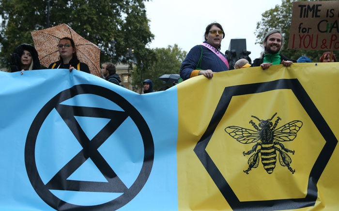 Climate change activists from the Extinction Rebellion block the road with a banner that calls on the government to act now to reduce greenhouse gas emissions to halt biodiversity loss and suggests the creation of citizen's assemblies on Whitehall outside Downing Street in central London, on 7 October 2019. Picture: AFP