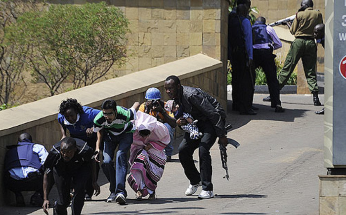 A policeman carry's a baby to safety after Somalia's al Shabaab terrorists stormed the Westgate Mall and sprayed gunfire on shoppers and staff in Nairobi, Kenya on 21 September 2013. Picture: AFP