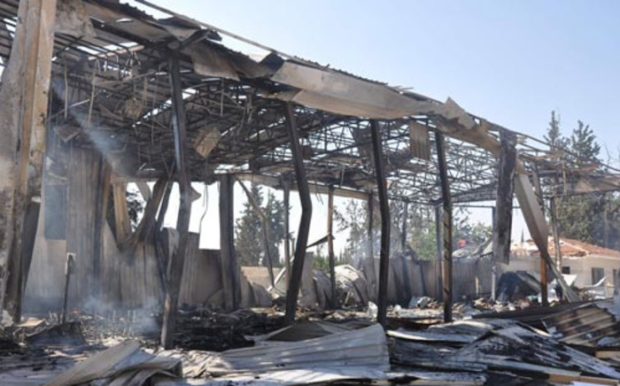 A small fire smolders (L) at the site of an attack on the pro-government Al-Ikhbariya satellite television channel's offices outside Damascus, which killed three staff on June 27, 2012. Picture: AFP
