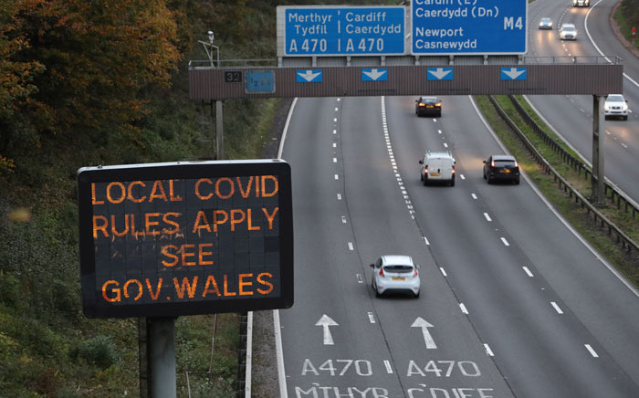 Traffic passes a COVID-19 sign displayed along the Cardiff-bound M4 motorway near Newport, in southeast Wales, as further restrictions come into force as the number of novel coronavirus COVID-19 cases rises. Picture: AFP