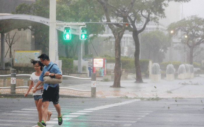 A couple crosses the street in the city centre of Naha, Okinawa prefecture, on 29 September 2018 as typhoon Trami is actually hitting Japan. Picture: AFP