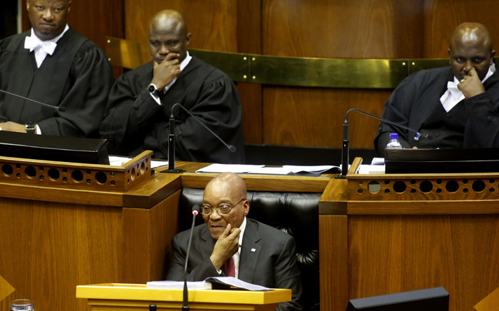 President Jacob Zuma sits down as he is interrupted trying to give his State of the Nation Address on 11 February 2016. Picture: AFP.