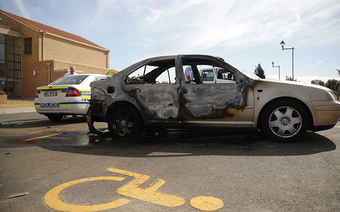 A burnt car and a police car at CPUT's Belville campus. Picture: Anthony Molyneaux/EWN.