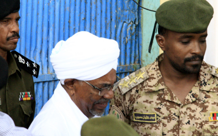 FILE: Omar al-Bashir is escorted before being driven in an armed convoy from the Kober prison to the prosecutor's office in North Khartoum on 16 June 2019. Picture: AFP