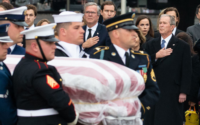 Former US President George W Bush and brother Jeb Bush wait as the casket of former US President George WH Bush is carried off the train upon arrival for the interment ceremony at the George HW Bush Presidential Library and Museum in College Station, Texas, on 6 December, 2018. Picture: AFP