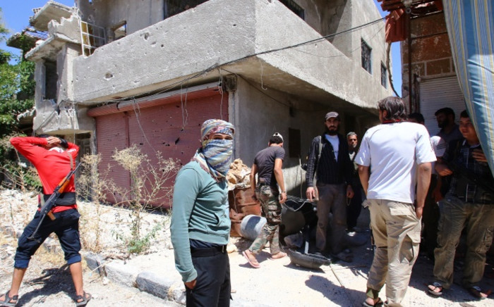 Rebel fighters who agreed to a truce with Syrian authorities gather on a street at the southern Damascus district of Qadam on 21 August 2014. Picture: AFP.