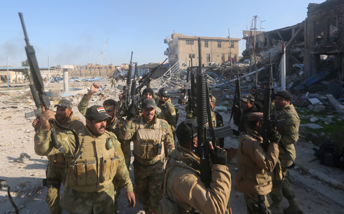 Iraqi security forces brandish their weapons on 28 December, 2015 at the heavily damaged Anbar police headquarters after they recaptured the city of Ramadi, the capital of Iraqs Anbar province, about 110 kilometers west of Baghdad, from Islamic States group jihadists. Picture: AFP.