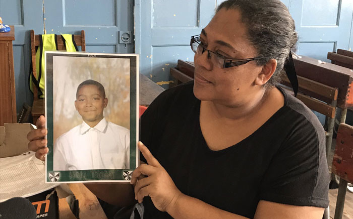 Amelia Bergoor was Adrian Alexander's teacher. Bergoor holds up a picture of her late student, who was killed in gang violence. Picture: Lauren Isaacs/EWN.