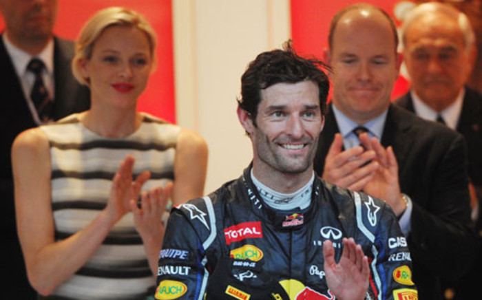 Red Bull Racing's Australian driver Mark Webber (C) celebrates on the podium as Prince Albert of Monaco and Princess Charlene (L) stand at the Circuit de Monaco on May 27, 2012. Picture: AFP