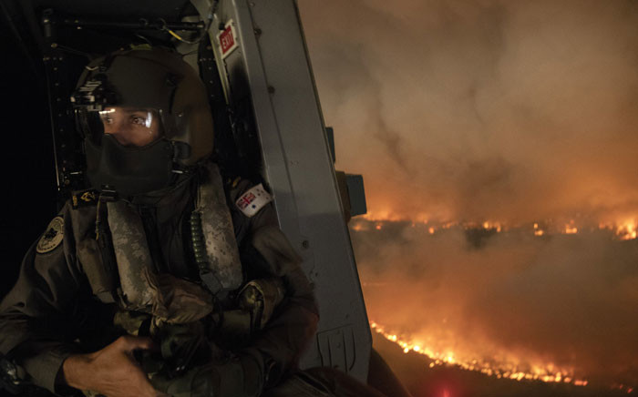 FILE: This handout photo taken on 21 December 2019 and obtained on 22 December from the Australia Department of Defence shows an aircrewman monitoring the Tianjara fire from a helicopter in the Moreton and Jerrawangala National Park in Moreton. Picture: AFP