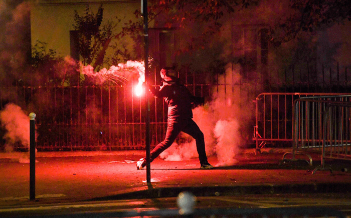 A Paris Saint-Germain (PSG) supporter holds a flare near the Parc des Princes stadium in Paris on August 23, 2020, after the UEFA Champions League final football match between PSG and Bayern Munich played at the Luz stadium in Lisbon. Picture: AFP