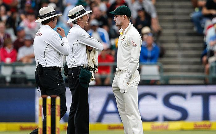 FILE: Australia's Cameron Bancroft is questioned by Umpires Richard Illingworth and Nigel Llong during the third day of the third Test cricket match between South Africa and Australia at Newlands cricket ground on 24 March 2018 in Cape Town. Picture: AFP