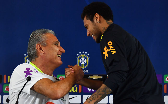 Brazil's footballer Neymar (R) shakes hands with team coach Tite (L) during a press conference after a training session on the eve of their 2018 FIFA Russia World Cup qualifier. Picture: AFP