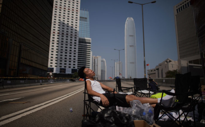 A pro-democracy protester sleeps on an empty road in the Admiralty district of Hong Kong early on 7 October, 2014. Picture: AFP.