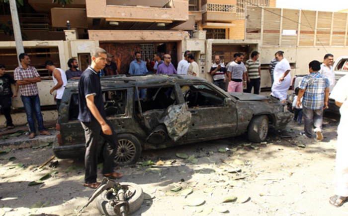 Bystanders gather at the scene of car bomb explosion outside the Swedish consulate in the eastern Libyan city of Benghazi on October 11, 2013. Picture: AFP