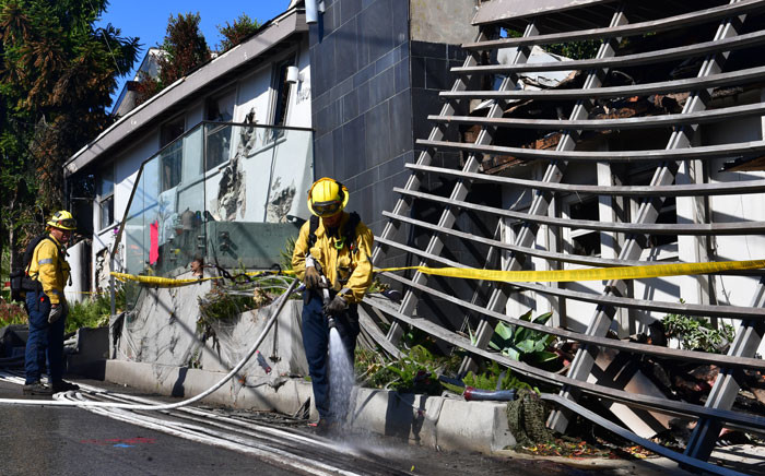 Firefighters outside destroyed homes along North Tigertail Road near The Getty Center in Los Angeles, California on 29 October 2019. Picture: AFP