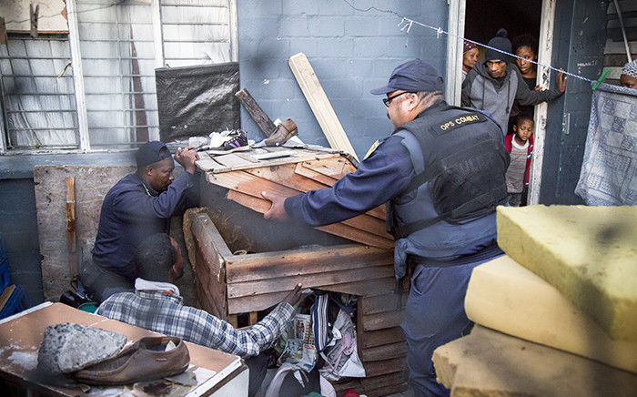 FILE: Residents of a house look on as police search for guns and drugs during a Fiela Operation in Ottery on 22 May 2015. Picture: Thomas Holder/EWN.