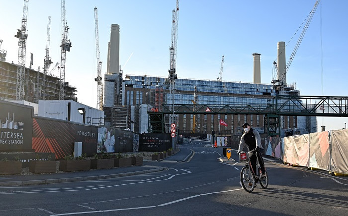 FILE: A man, wearing a face mask as a precautionary measure against COVID-19, cycles past the Battersea Power Station development in south London on 24 March 2020. Picture: AFP