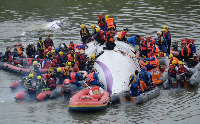 Rescue personnel work to free passengers from a TransAsia ATR 72-600 turboprop plane that crash-landed into a river outside Taiwan's capital Taipei in New Taipei City on February 4, 2015. Picture: AFP