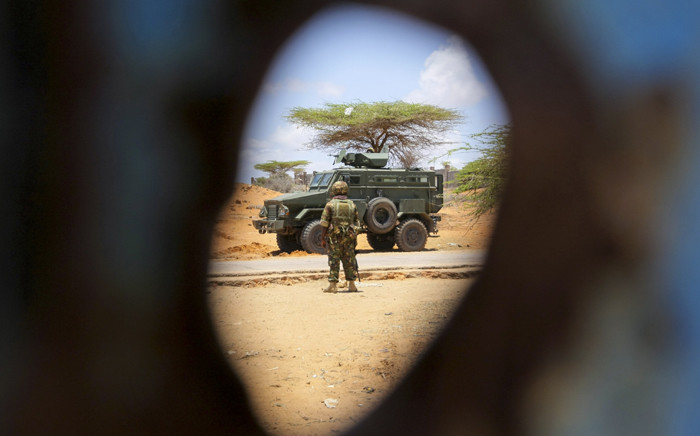 FILE: A Kenyan soldier serving with the AMISOM is pictured through a bullet hole in the gate of the compound housing the former offices of the UN's refugee agency in Kismayo, southern Somalia. Picture: UN Photo.