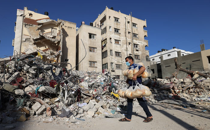 FILE: A Palestinian bakery worker holds bags of bread past the ruins of a building destroyed during the recent Israeli bombings, in Gaza City on 27 May 2021. Picture: Mohammed Abed/AFP