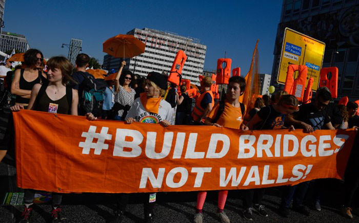 """Demonstrators hold a banner reading """"Build bridges not walls!"""" as they gather at Berlin's Alexanderplatz during a major demonstration for an open and caring society organised by the action group """"Unteilbar"""" (indivisible) on 13 October 2018. Picture: AFP."""