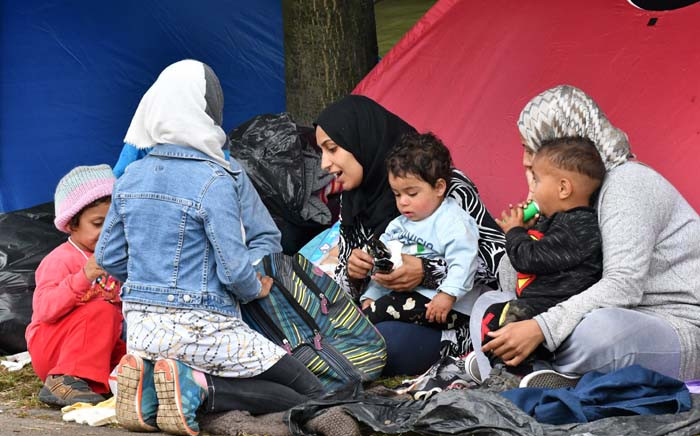 Migrant women with children sit outside their tent, in the park across from The City hall, in Bosnia Sarajevo on 14 May 2018. Picture: AFP.