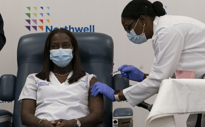 Sandra Lindsay(L), a nurse at Long Island Jewish Medical Centre, is inoculated with the COVID-19 vaccine by Dr Michelle Chester at Long Island Jewish Medical Centre on 14 December 2020 in the Queens borough of New York. Picture: AFP.