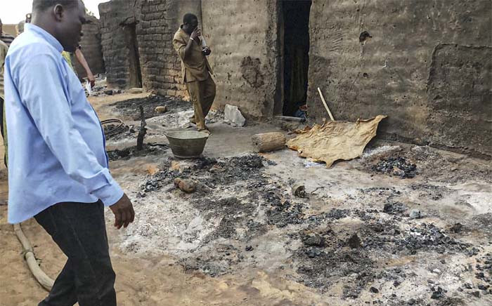 Officials and residents stand near ashes on 11 June 2019 in the Dogon village of Sobane-Kou, near Sangha, after a deadly attack on 9 June. Picture: AFP