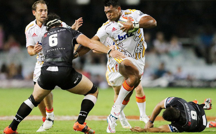 Seta Tamanivalu (C) of the Chiefs hands off Marcell Coetzee (L) and Cobus Reinach (R) of the Sharks to break a tackle during the SuperXV rugby match between Sharks and Chiefs on 21 March, 2015 in Durban. Picture: AFP