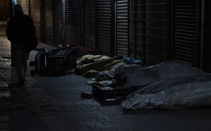FILE: A man walks past homeless people sleeping outside a shop. Picture: EWN