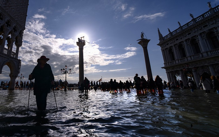A general view shows people walking across the flooded St Mark's Square, with the Doge's palace (L), the statue of the Lion of St. Mark (Rear L) and the Column of ST. Theodore of Amasea (Rear R) on 14 November 2019 in Venice. Picture: AFP