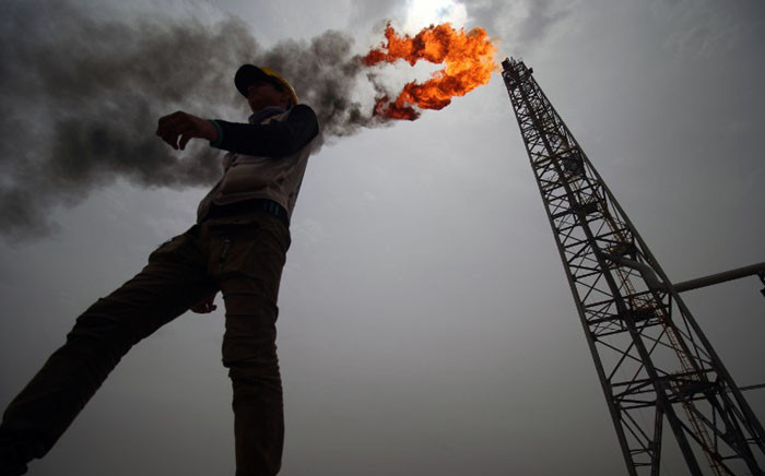 FILE: An employee walks at the Hammar Mushrif new Degassing Station Facilities site inside the Zubair oil and gas field, north of the southern Iraqi province of Basra on 9 May 2018.  Picture: AFP.