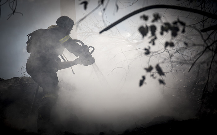 FILE: A firefighter uses water to dowse embers on Groot Constantia wine estate on 4 March 2015. Picture: Aletta Gardner/EWNa