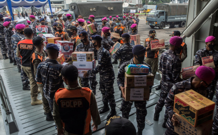 Indonesian Navy personnel load relief supplies for people affected by Tropical Cyclone Seroja onto the KRI Semarang (594) landing platform dock ship at Dermaga port in Surabaya, East Java, on April 10, 2021.