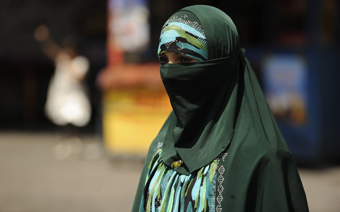 FILE: A Muslim ethnic Uighur woman walks on a street in Urumqi, capital of China's Xinjiang region ahead of the first anniversary of bloody violence that erupted between the region's Muslim ethnic Uighurs and members of China's majority Han ethnicity. Picture: AFP