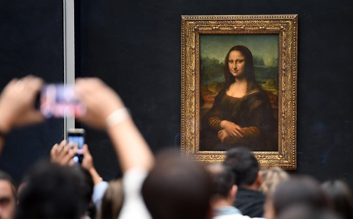 Visitors take pictures in front of 'Mona Lisa' after it was returned at its place at the Louvre Museum in Paris on 7 October 2019. Picture: AFP