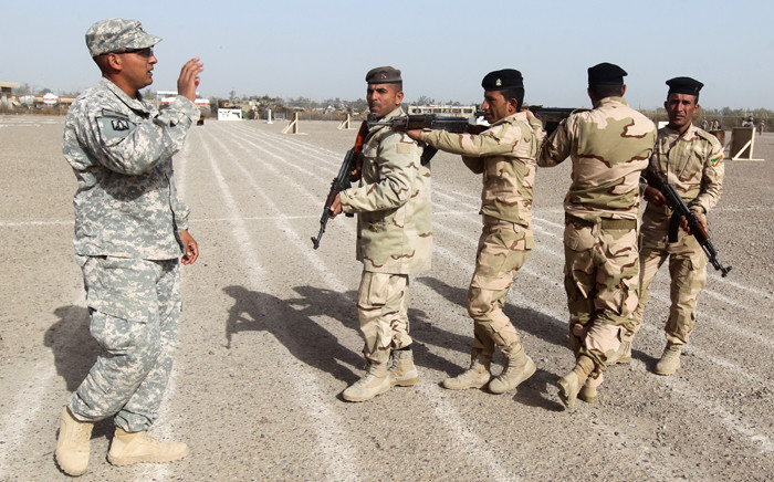 FILE: American military trainers show Iraqi soldiers how to work in a formation during a training session at the Taji base complex, which hosts Iraqi and US troops, located 30km north of the capital Baghdad. Picture: AFP.