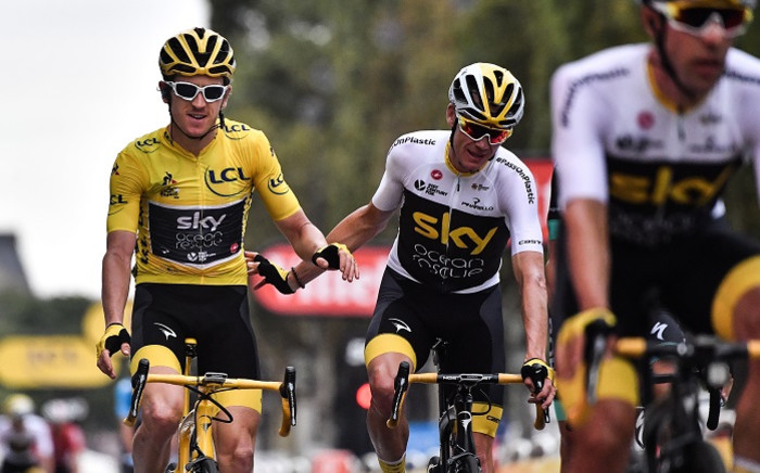 Tour de France winner Great Britain's Geraint Thomas (L) wearing the overall leader's yellow jersey and classification third-placed Great Britain's Christopher Froome (R) react as they cross the finish line, on July 29, 2018.  Picture: AFP