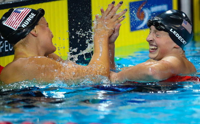 Katie Ledecky (R) and Cierra Runge (L) of the US react following the women's 400m freestyle final at the Gold Coast Aquatic Centre in Gold Coast on 23 August 2014. Picture: AFP/ PATRICK HAMILTON