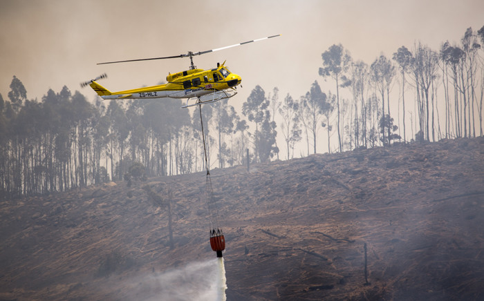 A Working on Fire helicopter water bombs a section of forest next to the vineyards of Muratie Wine Estate outside Stellenbosch as the region suffers a third day of battling the Simonsberg fire on 22 January 2016. Picture: Aletta Harrison/EWN.
