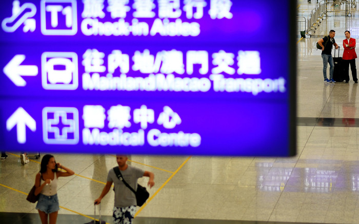 FILE: Passengers walk in the arrivals area after Hong Kong's International airport resumed operations early 13 August 2019. Flights resumed on 13 August at Hong Kong airport a day after a massive pro-democracy rally there forced the shutdown of the busy international transport hub. Picture: AFP.