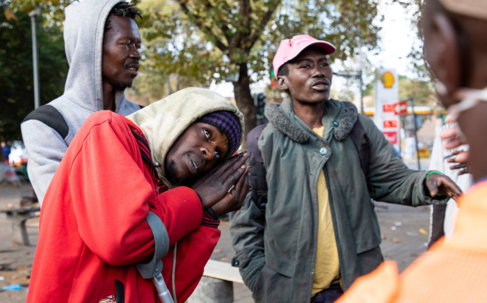 A homeless man explains to the police about how he cannot sleep in the streets without blankets. Picture: Ahmed Kajee/EWN