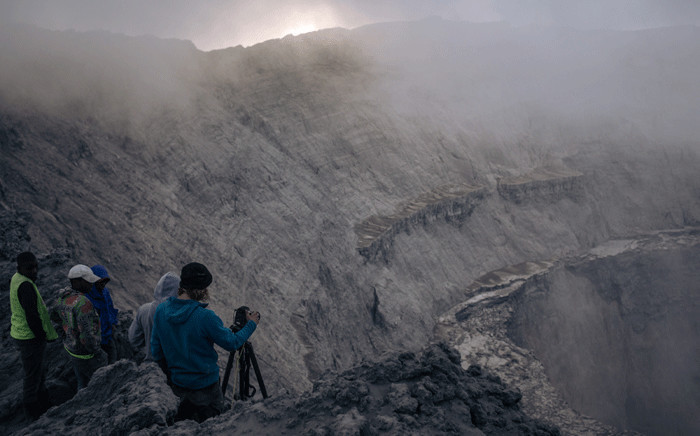 Christopher Horsley (R), a technical assistant to Congolese volcanologists, takes pictures into the crater of Nyiragongo volcano, north of Goma, the provincial capital of North Kivu, on June 11, 2021. Three weeks after Nyiragongo's May 22 eruption, which caused the death of about 30 people and the evacuation of nearly half a million residents of Goma, volcanologists from the Goma Volcanological Observatory climb to the top of the crater to assess volcanic activity. Picture: Alexis Huguet / AFP
