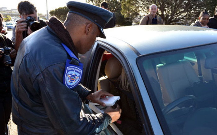 FILE: A traffic officer impounds a cellphone along Nelson Mandela Boulevard on 5 July 2012. Picture: Aletta Gardner/EWN