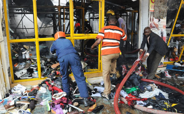 Members of the public assist firefighters work at the scene of a blast in central Nairobi on Moi Avenue on May 28, 2012. Picture: AFP