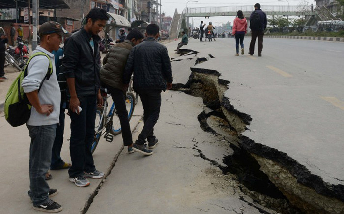 FILE: Nepalese residents walk past road damage following an earthquake in Kathmandu on 26 April, 2015. Picture: AFP.